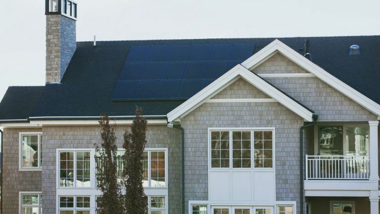 Solar Panels on a large seaside home with chimney and many windows.